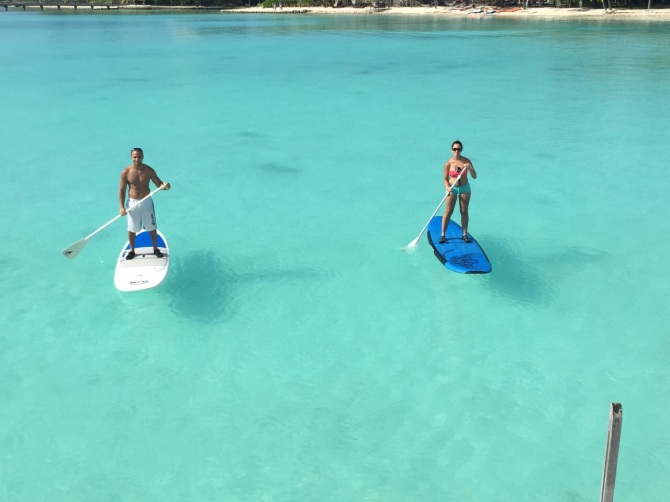 Paddle boarding in Bora Bora clear blue waters.