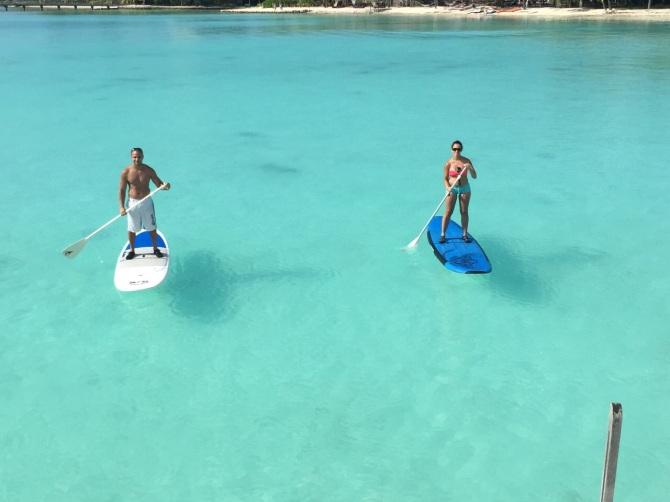 Paddle boarding in Bora Bora clear blue waters.